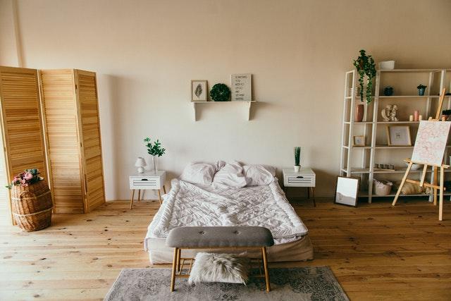 Presvetlená spálňa s drevenou podlahou, paravánom a moderným nábytkom