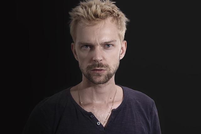 Muž v hnedom tričku, s blond vlasmi sa tvári tragicky.jpg
